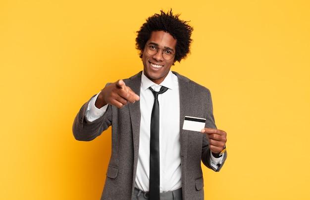 Junger schwarzer afro-mann, der mit einem zufriedenen, selbstbewussten, freundlichen lächeln nach vorne zeigt und sie wählt
