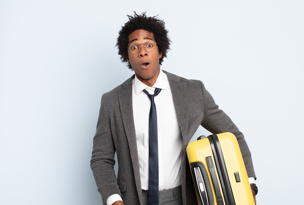 Junger schwarzer afro-mann, der sehr schockiert oder überrascht aussieht und mit offenem mund starrt und wow sagt