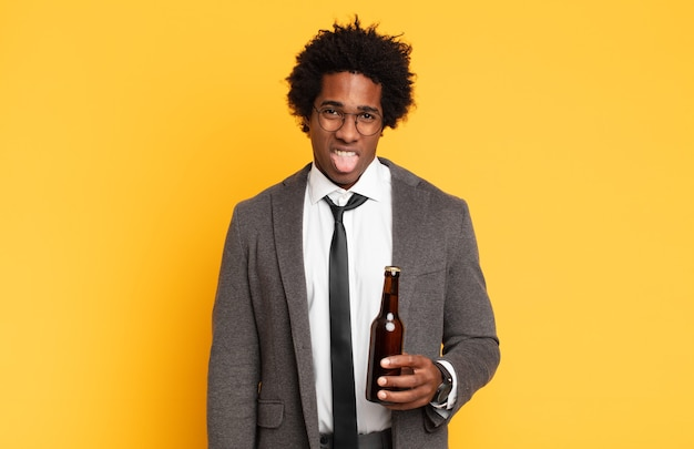 Junger schwarzer afro-mann, der sich angewidert und gereizt fühlt, die zunge herausstreckt und etwas böses und glückliches nicht mag
