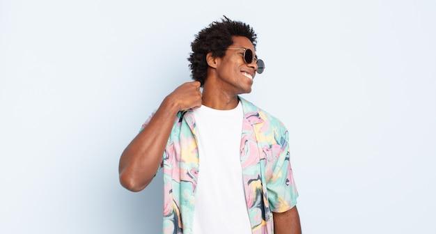 Junger schwarzer afro-mann, der sich gestresst, ängstlich, müde und frustriert fühlt, den hemdhals zieht und mit dem problem frustriert aussieht