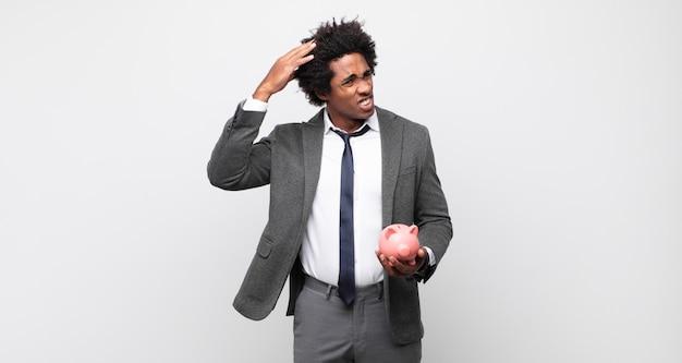 Junger schwarzer afro-mann, der sich gestresst, besorgt, ängstlich oder verängstigt fühlt, mit händen auf dem kopf, die bei einem fehler in panik geraten
