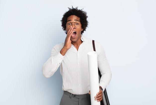 Junger schwarzer afro-mann, der sich glücklich, aufgeregt und positiv fühlt, mit den händen neben dem mund einen großen schrei ausstößt und ruft