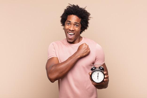 Junger schwarzer afro-mann, der sich glücklich, positiv und erfolgreich fühlt, motiviert, wenn er sich einer herausforderung stellt oder gute ergebnisse feiert