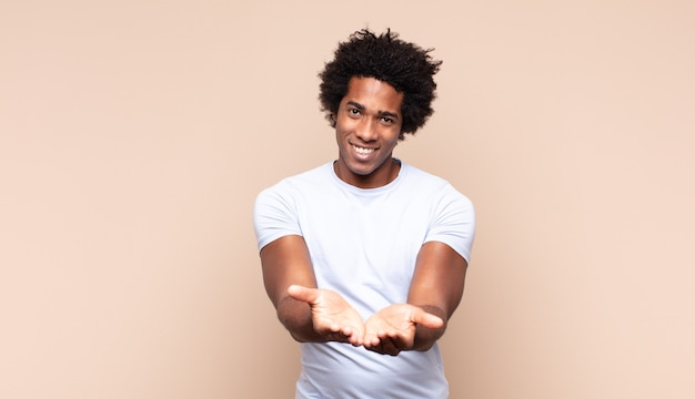Junger schwarzer afro-mann, der sich mit halsschmerzen und grippesymptomen krank fühlt und mit bedecktem mund hustet