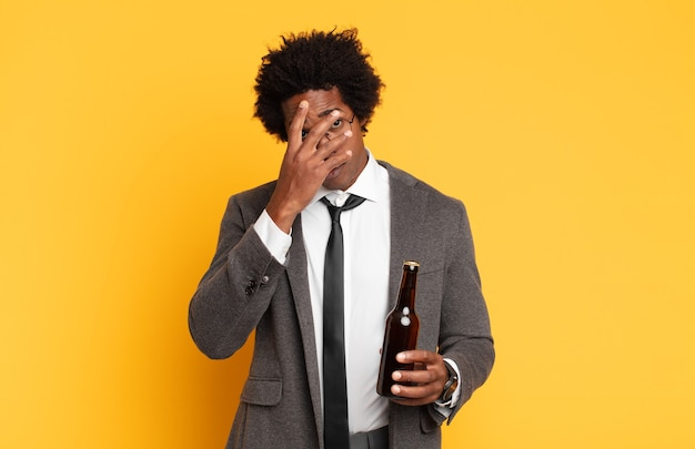 Junger schwarzer afro-mann, der sich nach einer ermüdenden, langweiligen und mühsamen aufgabe gelangweilt, frustriert und schläfrig fühlt und das gesicht mit der hand hält