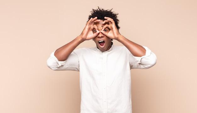 Junger schwarzer afro-mann, der sich schockiert, erstaunt und überrascht fühlt und eine brille mit erstauntem, ungläubigem blick hält