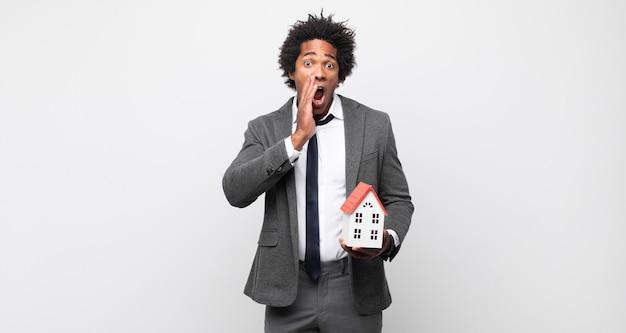 Junger schwarzer afro-mann, der sich schockiert und verängstigt fühlt und mit offenem mund und händen auf den wangen erschrocken aussieht