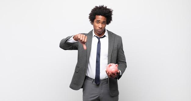 Junger schwarzer afro-mann, der sich verärgert, wütend, verärgert, enttäuscht oder unzufrieden fühlt und mit ernstem blick daumen nach unten zeigt