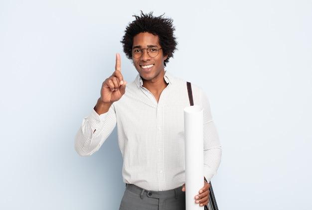 Junger schwarzer afro-mann, der stolz und selbstbewusst lächelt und nummer eins triumphierend posiert und sich wie ein anführer fühlt
