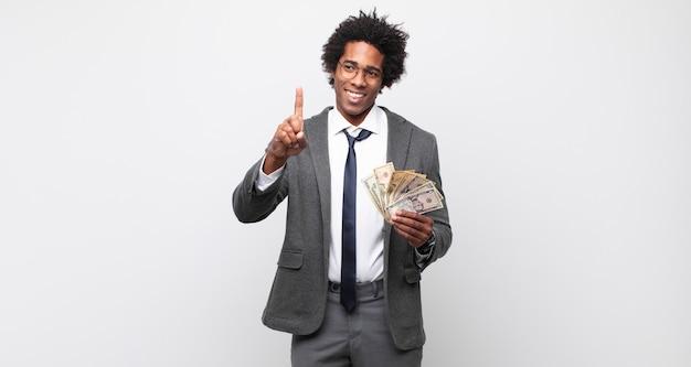 Junger schwarzer afro-mann, der stolz und zuversichtlich lächelt und nummer eins triumphierend posiert und sich wie ein anführer fühlt