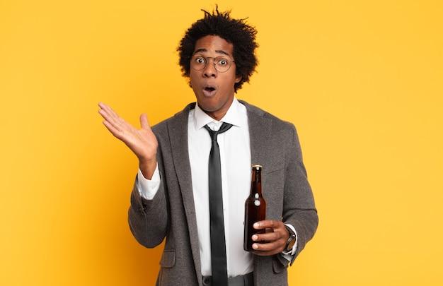 Junger schwarzer afro-mann, der überrascht und geschockt aussieht, mit gesenktem kiefer, der einen gegenstand mit einer offenen hand auf der seite hält