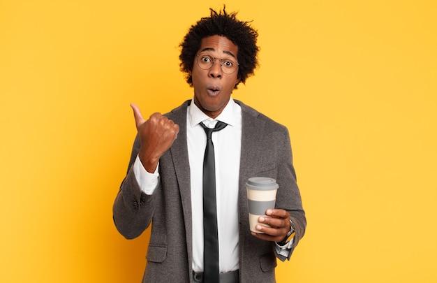 Junger schwarzer afro-mann, der ungläubig erstaunt aussieht, auf ein objekt an der seite zeigt und sagt, wow, unglaublich