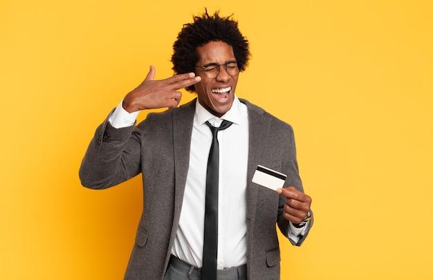 Junger schwarzer afro-mann, der unglücklich und gestresst aussieht, selbstmordgeste, die waffenzeichen mit der hand macht und auf den kopf zeigt