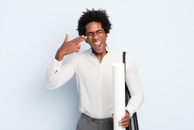 Junger schwarzer afro-mann, der unglücklich und gestresst aussieht, selbstmordgeste, die waffenzeichen mit hand macht, zeigt auf kopf