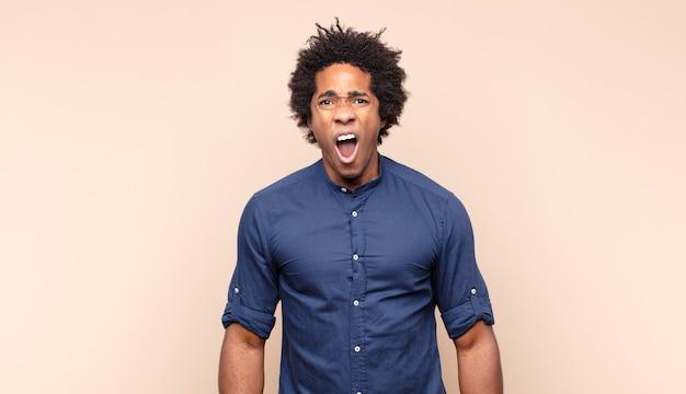 Junger schwarzer afro-mann, der wütend, genervt und frustriert schreiend aussieht