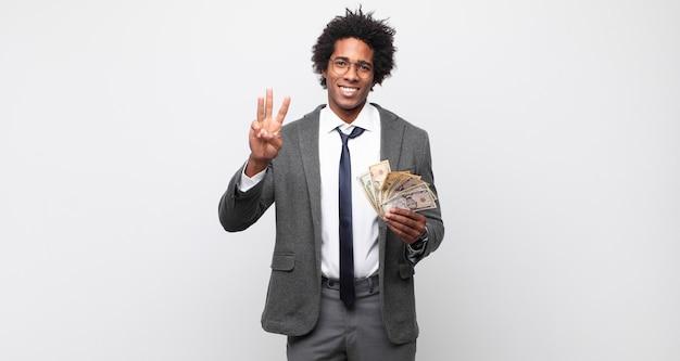 Junger schwarzer afro-mann lächelt und sieht freundlich aus, zeigt nummer drei oder dritte mit der hand nach vorne, countdown