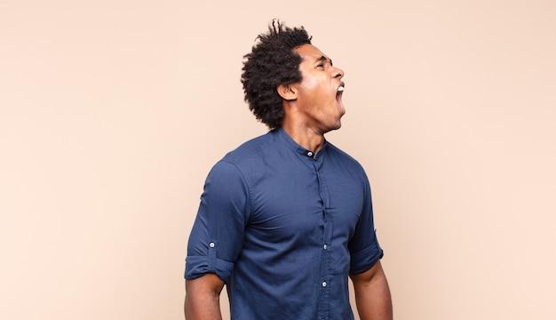 Junger schwarzer afro-mann mit einem albernen, verrückten, überraschten gesichtsausdruck, schnaufenden wangen, sich vollgestopft, fett und voller essen zu fühlen