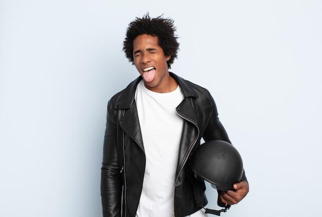 Junger schwarzer afro-mann mit fröhlicher, sorgloser, rebellischer haltung, scherzend und zunge herausstreckend, spaß habend