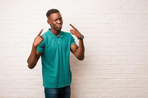 Junger schwarzer afroamerikaner mit einer schlechten haltung, die stolz und aggressiv aussieht, nach oben zeigt oder spaßzeichen mit den händen gegen backsteinmauer macht