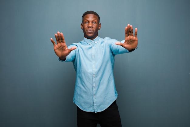 Junger schwarzer afroamerikanermann, der ernst, unglücklich, wütend und unzufrieden aussieht, den eintritt zu verbieten oder stopp mit beiden offenen handflächen zu sagen