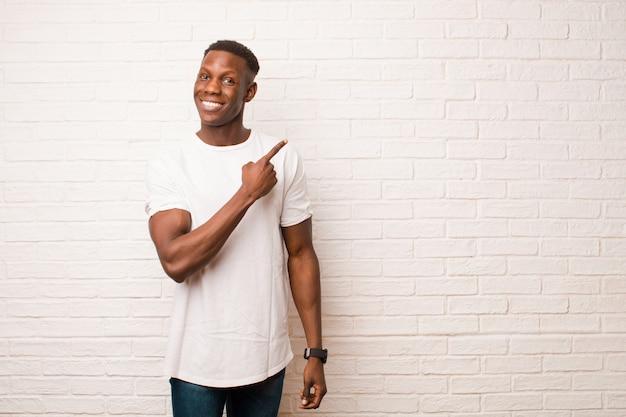 Junger schwarzer afroamerikanermann, der fröhlich lächelt, sich glücklich fühlt und zur seite und nach oben zeigt, objekt im kopienraum gegen backsteinmauer zeigend