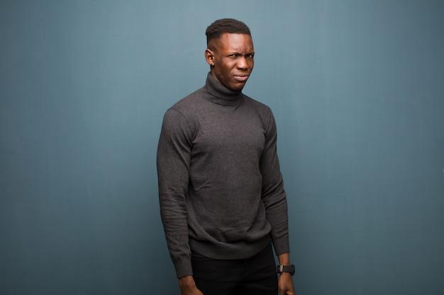 Junger schwarzer afroamerikanermann, der glücklich und freundlich schaut, lächelt und ein auge auf sie mit einer positiven haltung gegen schmutzwand zwinkert