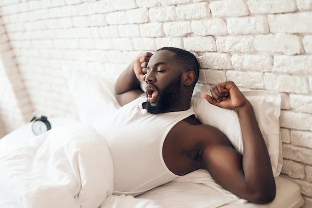 Junger schwarzer, aufgeweckter mann liegt ausgestreckt im bett.