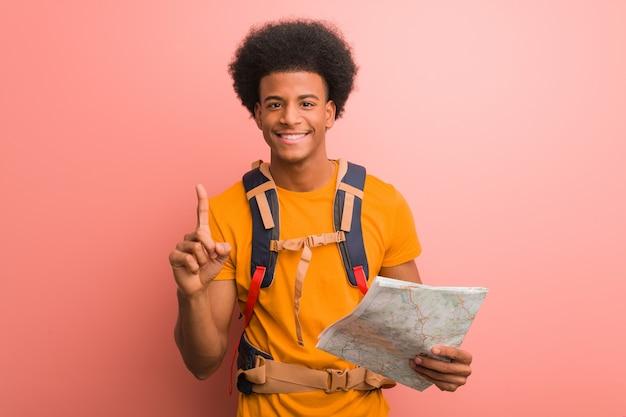 Junger schwarzer forschermann, der eine karte zeigt nummer eins hält