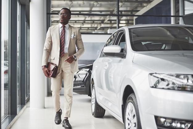 Junger schwarzer geschäftsmann auf autosalon. autoverkaufs- und mietkonzept. reicher afroamerikaner.