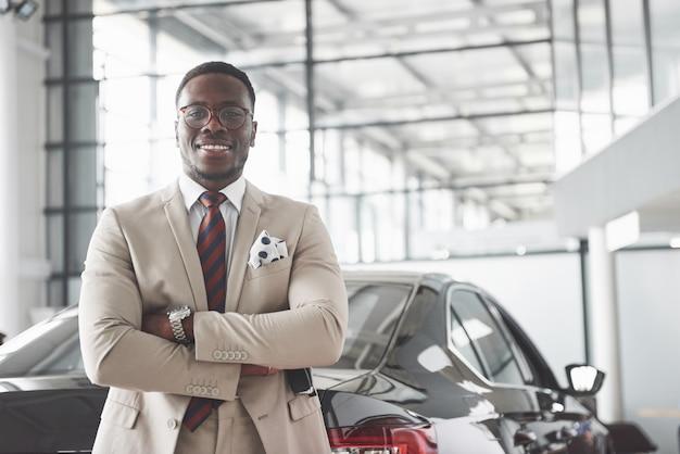 Junger schwarzer geschäftsmann auf autosalon. autoverkaufs- und mietkonzept.