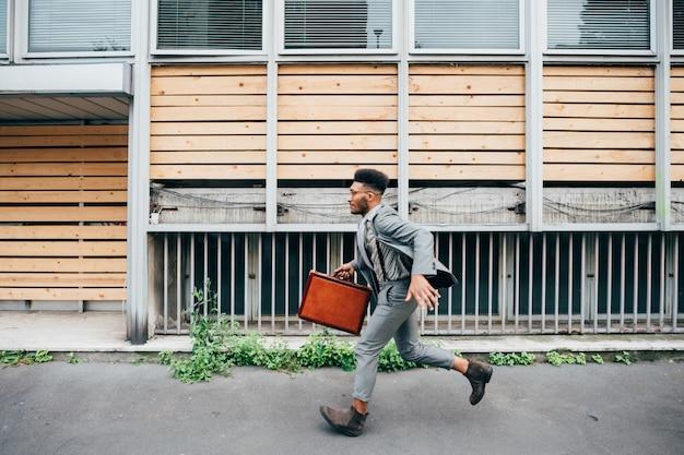Junger schwarzer geschäftsmann, der aktentasche hält, die draußen läuft