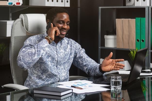 Junger schwarzer geschäftsmann, der am handy sitzt am computertisch im büro spricht