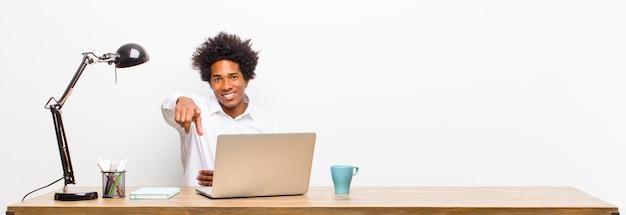 Junger schwarzer geschäftsmann, der auf kamera mit einem erfüllten, überzeugten, freundlichen lächeln, sie auf einem schreibtisch wählend zeigt