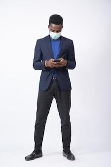 Junger schwarzer geschäftsmann, der einen anzug und eine gesichtsmaske trägt und sein telefon vor einem weißen benutzt