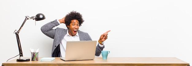 Junger schwarzer geschäftsmann, der lacht, glücklich, positiv und überrascht schaut und eine großartige idee verwirklicht, die auf seitlichen kopienraum auf einem schreibtisch zeigt
