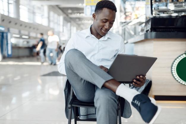 Junger schwarzer geschäftsmann, der laptop im autoausstellungsraum benutzt. erfolgreiche geschäftsperson auf der automobilausstellung, schwarzer mann in der abendgarderobe