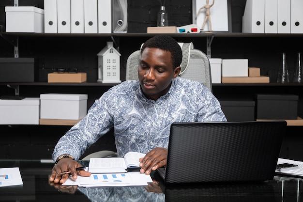 Junger schwarzer geschäftsmann, der mit dokumenten und laptop im büro arbeitet