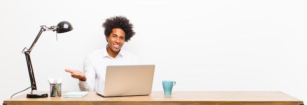 Junger schwarzer geschäftsmann, der nett lächelt, ein im copyspace mit palme der hand auf einem schreibtisch glücklich sich fühlt und zeigt