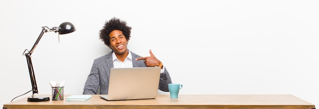 Junger schwarzer geschäftsmann, der stolz, überzeugt und glücklich schaut, auf selbst lächelt und zeigt oder nummer eins-zeichen auf einem schreibtisch macht