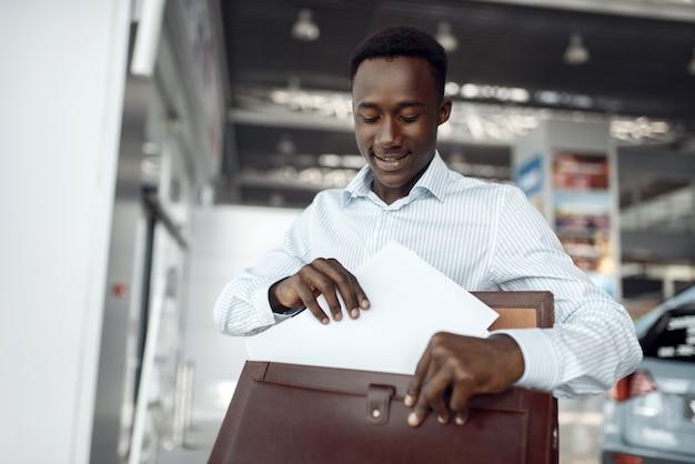 Junger schwarzer geschäftsmann hält aktentasche im autohaus. erfolgreiche geschäftsperson auf der automobilausstellung, schwarzer mann in der abendgarderobe