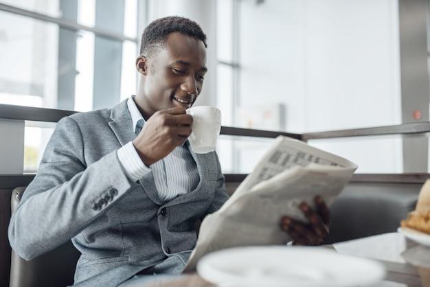 Junger schwarzer geschäftsmann mit zeitung, die im bürocafé zu mittag isst. erfolgreicher geschäftsmann trinkt kaffee im food-court, schwarzer mann in formeller kleidung