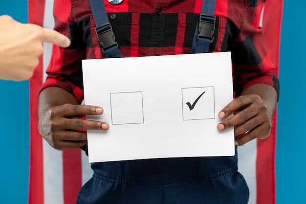 Junger schwarzer handwerker, der stimmzettel mit zecke im quadrat hält, während gegen amerikanische flagge steht