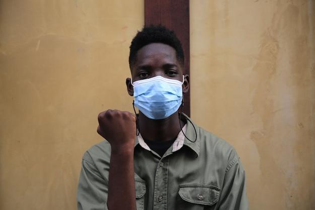 Junger schwarzer hautmann mit gesichtsmaske zur vorbeugung des covid-19-virus.