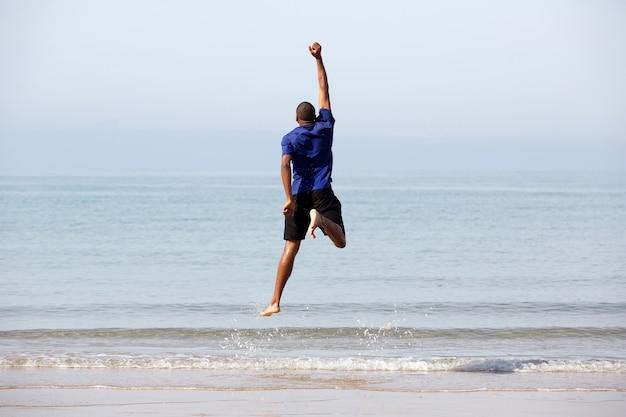 Junger schwarzer kerl, der durch den strand springt