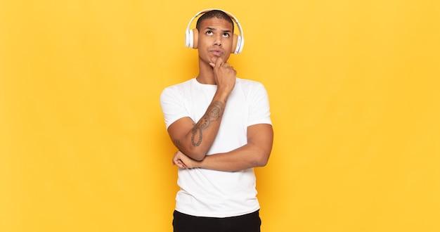 Junger schwarzer mann denkt, fühlt sich zweifelhaft und verwirrt, hat verschiedene möglichkeiten und fragt sich, welche entscheidung er treffen soll