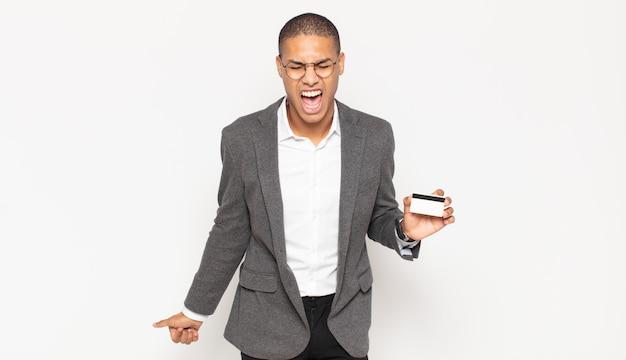 Junger schwarzer mann, der aggressiv schreit, sehr wütend, frustriert, empört oder genervt aussieht und nein schreit