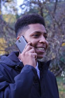 Junger schwarzer mann, der am intelligenten telefon im wald spricht.