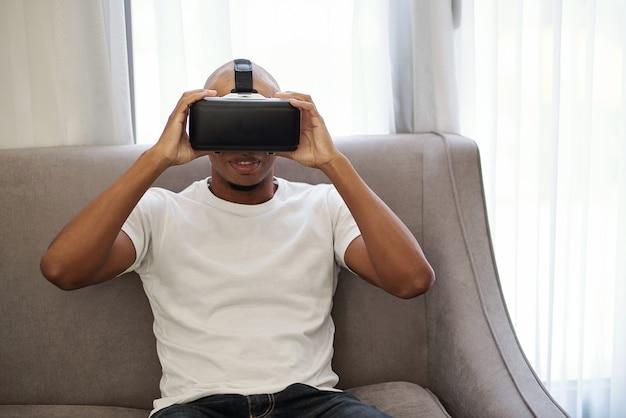 Junger schwarzer mann, der auf bequemem sofa zu hause sitzt und neues virtuelles realitätsspiel genießt