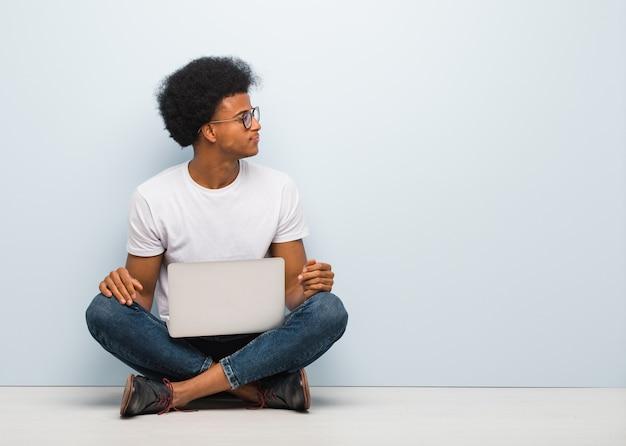 Junger schwarzer mann, der auf dem boden mit einem laptop auf der seite schaut nach vorne sitzt