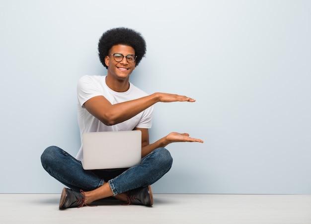 Junger schwarzer mann, der auf dem boden mit einem laptop hält etwas sehr überrascht und entsetzt sitzt